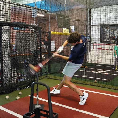 hitting-off-tee-in-batting-cage